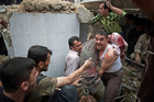 Syrian men rescue a person who was trapped in the rubble of the Nur al-Shuhada mosque in the Shaar district after it was shelled by forces loyal to President Bashar al-Assad on Oct 17. Photo / AFP