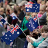 Jemma Roberts, 3, bottom right, holds an Australian flag as she and her father Scott watch a march commemorating ANZAC Day in Sydney, Australia. Photo / AP
