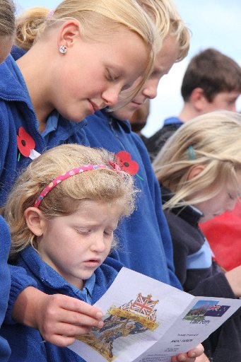 Kahutara School pupils Danielle Rose, 10 (top) and Zara Williams, 6, share a hymn sheet to sing Abide With Me during Lake Ferry's Anzac Day service.