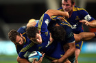 John Hardie of the Highlanders is tackled by Nic White of the Brumbies. Photo / Getty Images