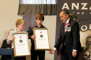 Governor-General Sir Jerry Mateparae presents Will White (left) and Sergio Schuler with their Anzac of the Year Awards in Waihi yesterday. Photo / Christine Cornege