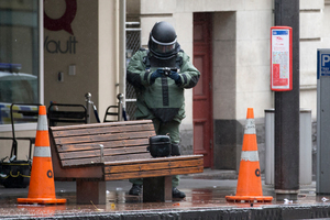 A Defence Force member photographs a suspicious package in Queen St.  Photo / Greg Bowker