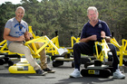 Peter Lietz, left, and David Hutcheson on the soon to be donated diggers. Photo / Michael Craig