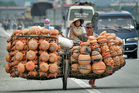 A Vietnamese man pushes a full load of clay pots along what was once the Ho Chi Minh trail, Vietnam. Photo / AP
