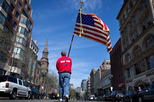 A fireman carries an American flag down Boylston St after observing a moment of silence to remember the victims of the Boston Marathon bombings.  Photo / AP