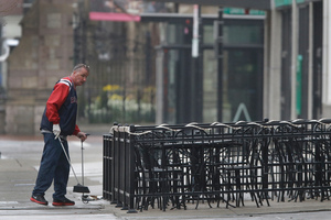 A man sweeps around the outdoor seating area on Boylston St in Boston as business owners prepare to reopen. Photo / AP