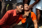 Bangladeshi rescuers squeeze through a gap to help pull out survivors (above) and relatives mourn a victim. Photo / AP