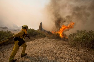 A firefighter rushes to extinguish the wildfire in the Naval Base at Point Mugu, Calif. Photo / AP