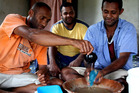 Tony (far right) accepts a bowl of traditional Fijian kava. Photo / Derek Cheng