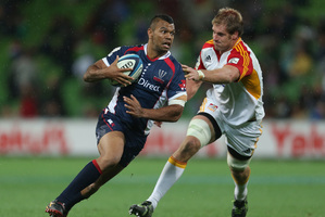 Kurtley Beale ran in one of the five Rebels tries on Friday night despite the best efforts of Craig Clarke. Photo / Getty Images