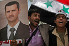 A Yemeni man holds a poster of Syrian president Bashar Assad. Photo / AP