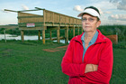 Papamoa resident Kay Harris and the unfinished bridge that would be useless in a tsunami.  Photo / Andrew Warner