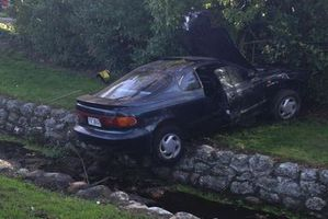 The car straddles a stream after its driver apparently suffered a seizure. Photo / Savannah Winter
