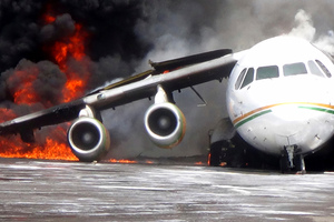 Smoke billows from a British-made BAe 146 cargo plane that caught fire while being unloaded at the airport in Wamena, Papua province, Indonesia. Photo / AP