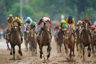 Orb (centre, white and red) splashes through the mud to win the Kentucky Derby. Photo / AP
