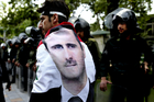 An Syrian man wrapped in a Syrian flag with a portrait of President Bashar Assad, walks past anti riot police during an anti-Israeli demonstration in Iran. Photo / AP