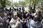 Pastor Larry Harris, center, leads a prayer vigil near the home where three women held captive for a decade, in Cleveland, Ohio. Photo / AP