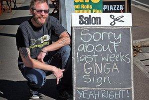 Scarlet Hair Studio owner Tavis Brush with the offending sign. Photo / Andrew Warner
