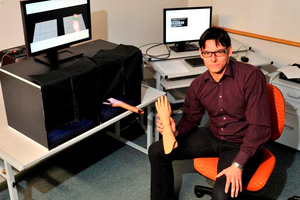 University of Otago graduand Simon Hoermann holds a rubber hand used in a new computer system to aid post-stroke rehabilitation. Photo / Linda Robertson