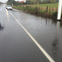 A puddle covers the footpath and half a lane on Hobsonville Road in Auckland. Photo / Emma Williams