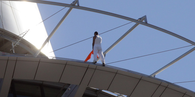 The man uses his jacket to balance on the side of the Sky Tower rim. Photo / Doug Sherring