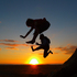 Sol, 9, and his father Sila Savila, jump over the setting sun at Karekare beach. Photo / Sarah McCarthy