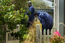 Investigators check a property in relation to the fatal stabbing of Murray Wilkinson outside this house. Photo / Alan Gibson