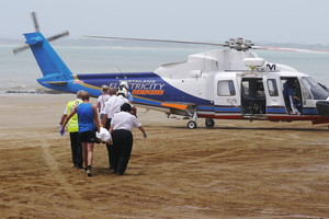 An injured man is tended by Northland Electricity rescue helicopter staff. Photo / C Pinkney