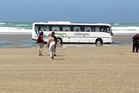 Tourists were off-loaded after one of the five buses became stuck in soft sand on Ninety Mile Beach. Photo / Anthony Mildren