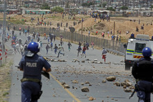 Striking farm workers run away from South African police after they fired rubber bullets at demonstrators in De Doorns, South Africa. Photo / AP