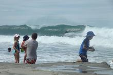 A surfer catches a big wave at Waipu. Photo / Rachael Snook