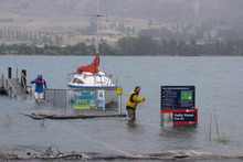 Wanaka holiday-makers Brett Gawn and his wife, Fay Paterson, wade through the rising water to remove their boat from Lake Wanaka. Photo / Lucy Ibbotson