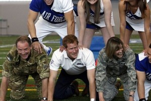 Prince Harry grimaces at the bottom of a pyramid of cheerleaders, US and British military officials. Photo / AFP