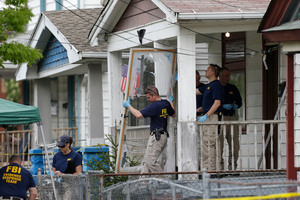Members of the FBI evidence response team carry out the front screen door from the house where three women were held captive, in Cleveland. Photo / AP
