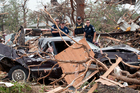 Emergency personnel look through debris on near Granbury, Texas after ten tornadoes touched down in several small communities in Texas, leaving at least six people dead. Photo / AP