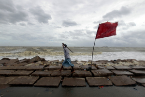 A Bangladeshi volunteer holding a stick walks along the Bay of Bengal coast to evacuate people in Chittagong, Bangladesh. Photo / AP