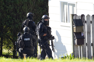 Auckland Armed Offenders Squad surround an Albany Highway address during an operation on Auckland's North Shore. Photo / Richard Robinson