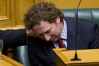 National MP Aaron Gilmore is comforted by colleague Cam Calder as he slumps down in his seat after reading his personal statement to the House after question time. Photo / Mark Mitchell