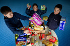 Andrew Leef, 13, Hineataarau Kohu, 10, and Damon Maireroa help to pack a food parcel at Randwick Park School in Manurewa as part of its food bank programme. Photo / Sarah Ivey