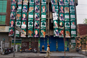 A Lahore building is covered in posters of once-exiled Nawaz Sharif, who has made a remarkable comeback from the political graveyard. Photo / AP