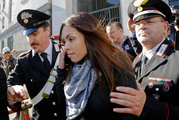 Karima el-Mahroug's is escorted outside the Milan's Law court after giving her testimony at the trial of three former Berlusconi aides accused with procuring her.Photo / AP