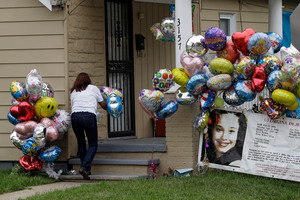 Culema Nevarez adds balloons to a growing tribute outside the house of Gina DeJesus. Photo / AP
