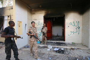 Libyan military guards check one of the U.S. Consulate's burnt out buildings during a visit by Libyan President Mohammed el-Megarif. Photo / AP