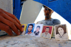 Issam, Adel Khedri's older brother, shows photos of (from left) Adel, Latifa and Habib. The woman at the right is unidentified. Above, a Bahraini fisherman.  Photo / AP