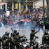 Demonstrators run away from tear gas fired by police after a march by striking miners ended in clashes in La Paz, Bolivia. Photo / AFP