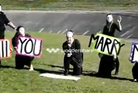 This is how Nicole Witt (centre) asked boyfriend Todd Eckersley to marry her. Image / YouTube