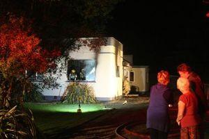 Residents watch as firefighters work on the house in Masterton. Photo / Lynda Feringa