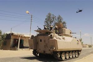 Egyptian Army soldiers patrol in an armoured vehicle backed by a helicopter gunship during a sweep through villages in in Sheikh Zuweyid, northern Sinai. Photo / AP