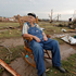 Gene Tripp sits in his rocking chair where his home once stood after being destroyed by a tornado hit the area near 149th and Drexel in Oklahoma City. Photo / AP
