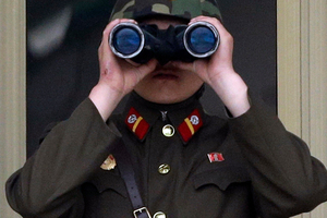 A North Korean soldier looks at the south side through a pair of binoculars at the border village of Panmunjom.Photo / AP